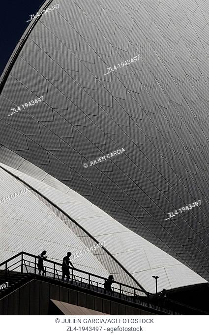 Silhouettes in front of Sydney Opera House and its wonderful curves. Australia, New South Wales, Sydney