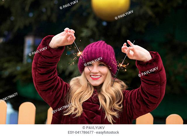 Joyful young woman holding glowing Bengal lights at the main Christmas tree in Kyiv. Blur effect