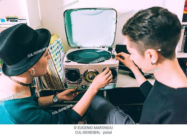 Over shoulder view of two young women playing vinyl on vintage turntable