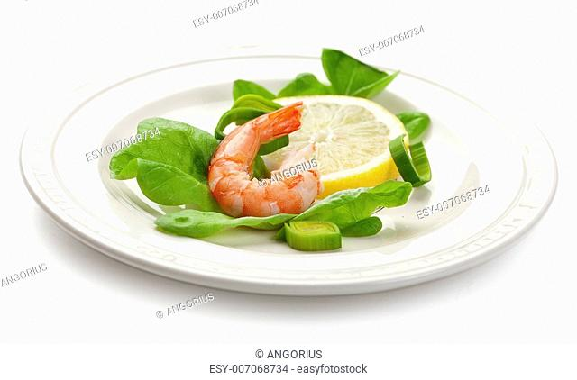 One shrimp's tail with lettuce, leek and lemon on the white plate