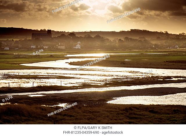 View of coastal wetland habitat and village with church at sunset, Salthouse, Norfolk, England, November