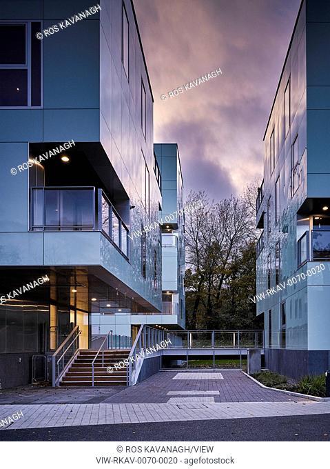 Dusk view of exterior showing stairway and walkway. Dunluce Apartments, Ballsbridge, Ireland. Architect: Derek Tynan Architects, 2016