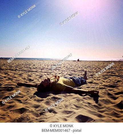 Caucasian man laying on beach