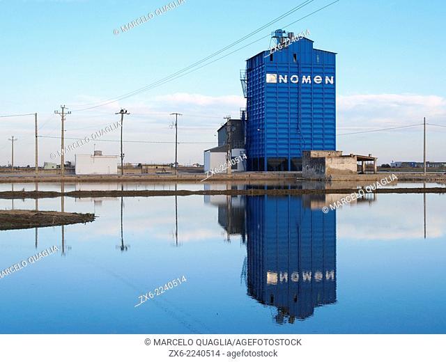 Rice silo reflection over flooded rice fields. Ebro River Delta Natural Park, Tarragona province, Catalonia, Spain