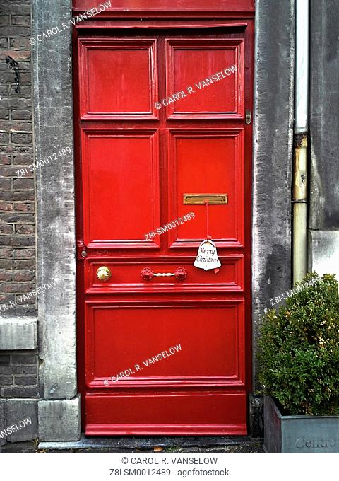 Red door on apartment with Christmas decoration hanging from mail slot, on side street in Maastricht