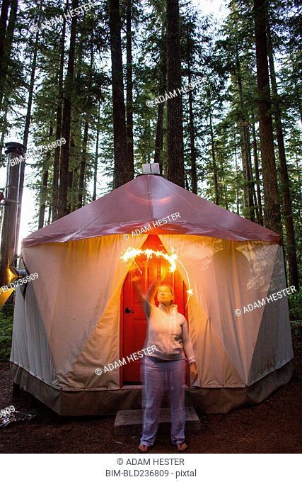 Caucasian woman waving sparkler outside yurt