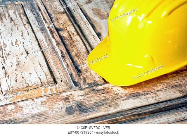 Yellow helmet on burnt wooden log