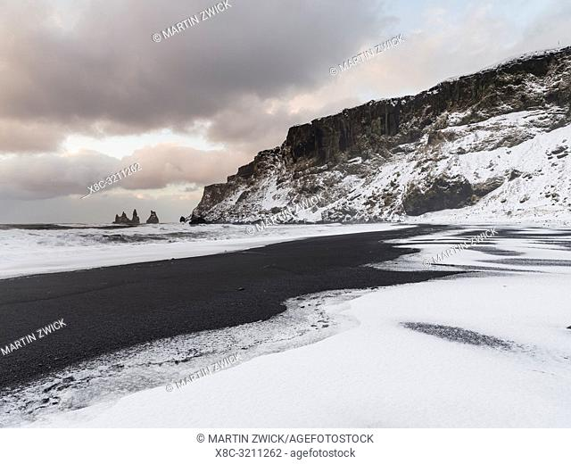 The coast of the north atlantic near Vik y Myrdal during winter. Black volcanic beach with the sea stacks Reynisdrangar. Europe, Northern Europe, Scandinavia