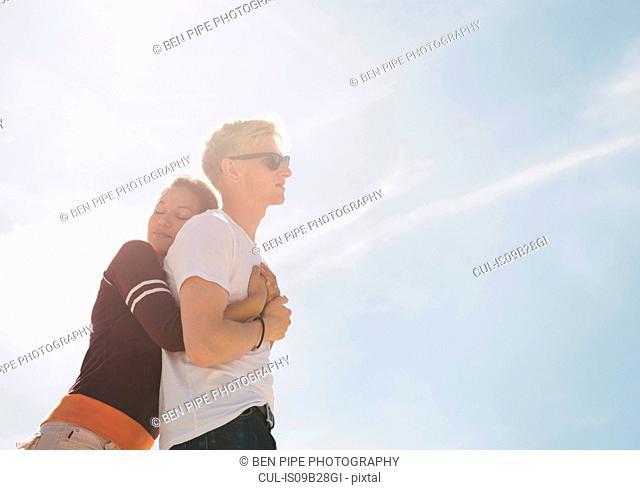 Woman hugging boyfriend against sunlit blue sky