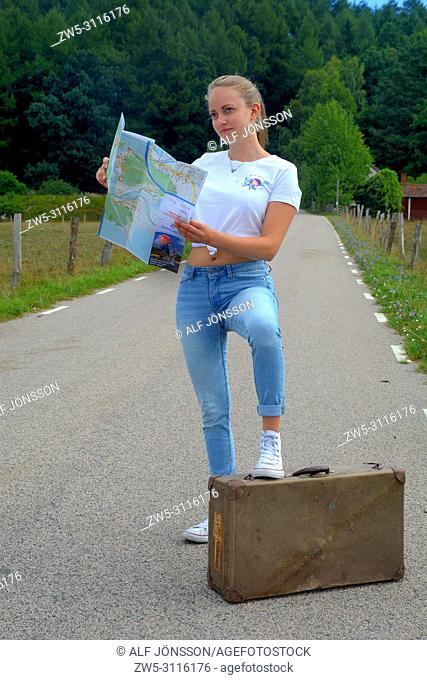 Young woman 25 years old, read a map standing with one foot on an old suitcase on a country road in Scania, Sweden, Europe
