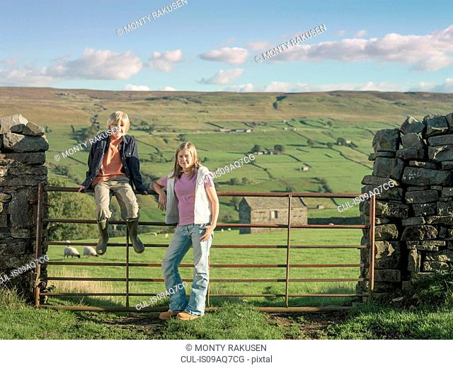 Teenage girl and brother at gate in rural landscape