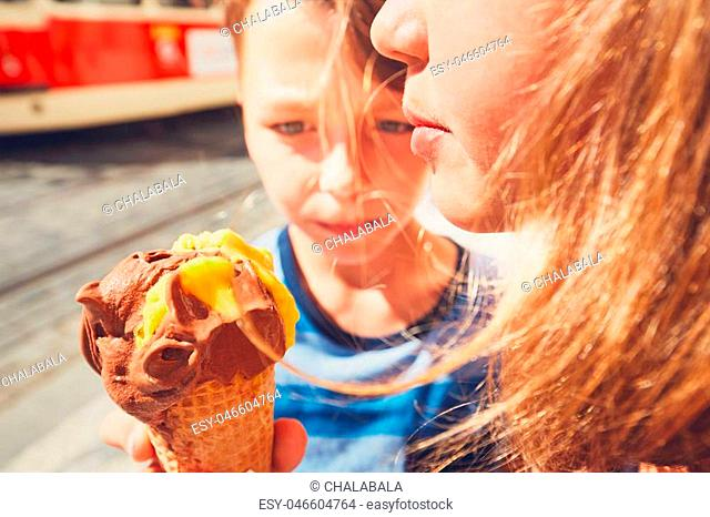 Summer day in the city. Cute siblings with hats eating big ice cream. Selective focus on the mouth