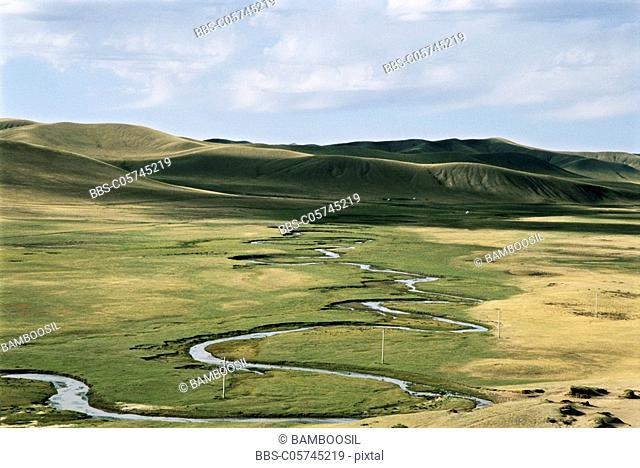 Elevated view of meandering stream passing through grassland, Bayangaole Prairie, Keshiketengqi, Chifeng City, Inner Mongolia Autonomous Region of People's...