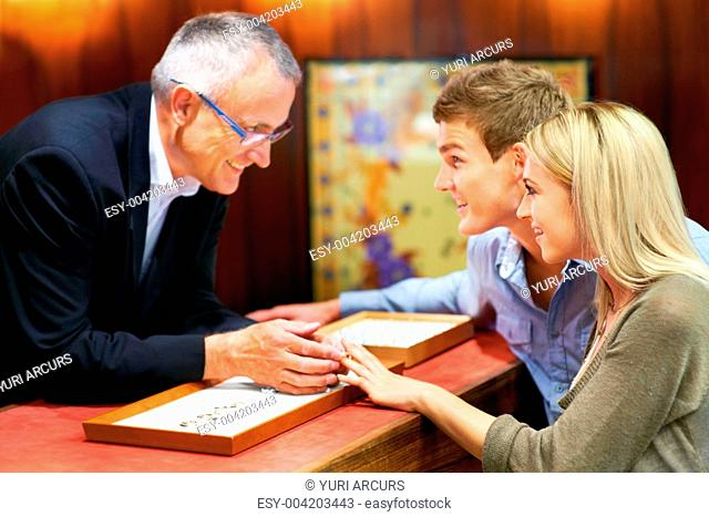 Mature clerk helping a young couple choose a ring in a jewellery store