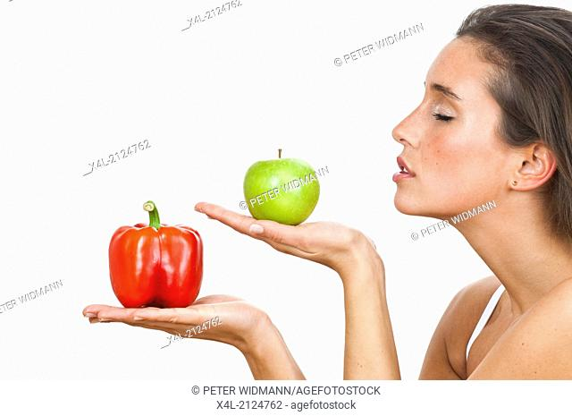 Young woman with red pepper and green apple (model-released)