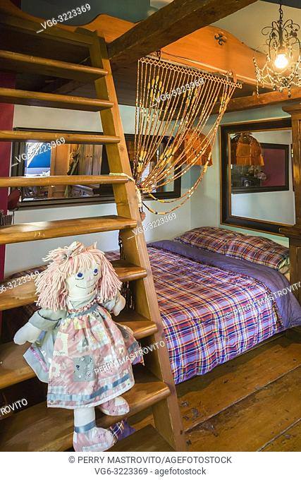 Rag doll sitting on wooden bunk bed ladder in child's bedroom on the upstairs floor inside an old circa 1850 Canadiana cottage style home