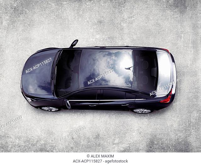 High angle view of the top of a black Cadillac XTS luxury car on gray concrete pavement view from above. Isolated with clipping path