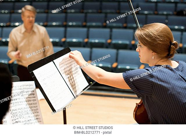 Student reading sheet music on stage