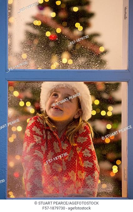 Young girl looking out of the window waiting for Santa to arrive