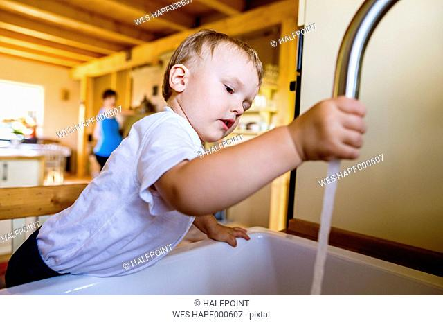 Little boy playing with tap in kitchen