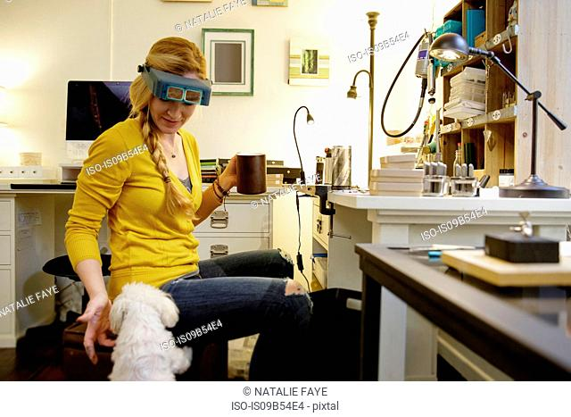 Female jewellery maker petting dog in design studio