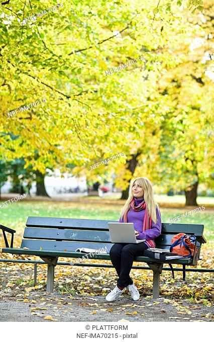A woman sitting on bench in a park using a laptop Stockholm Sweden