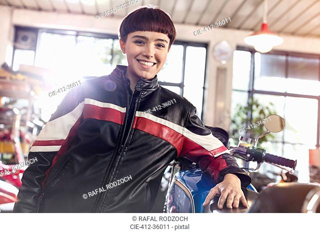 Portrait confident female motorcycle mechanic in workshop
