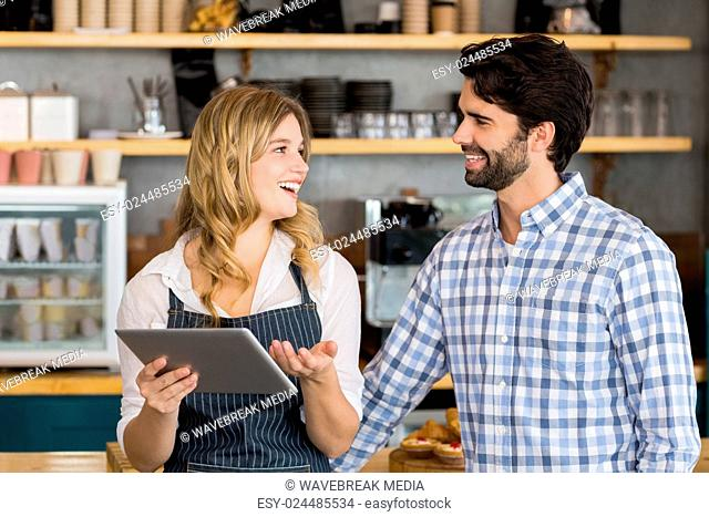 Smiling man and waitress standing at counter using digital tablet