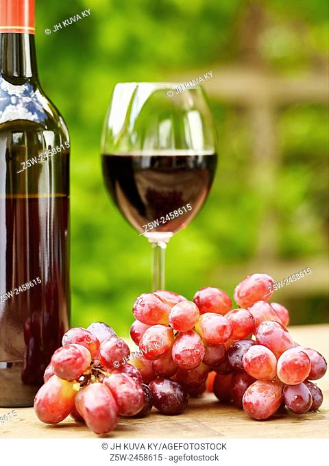 Red Wine, Glass and Grapes on the table - focus on grapes, vertical format