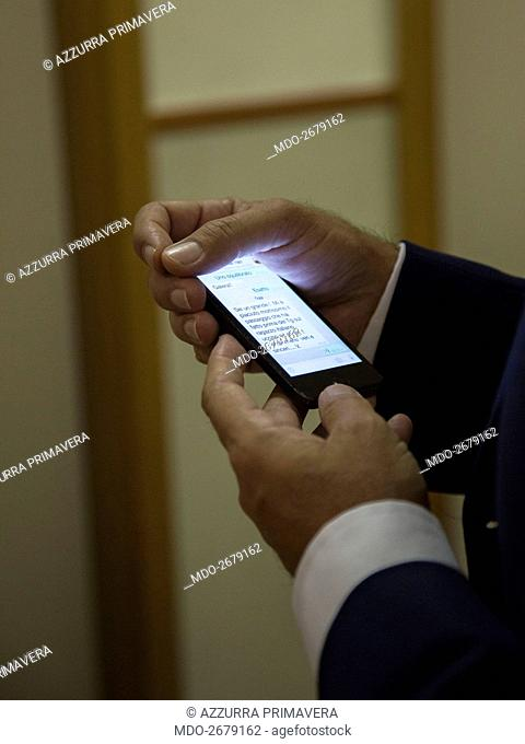 Baskstage of the TV show 'Unomattina': detail of the switched on cell phone in the hands of Italian TV host Franco Di Mare