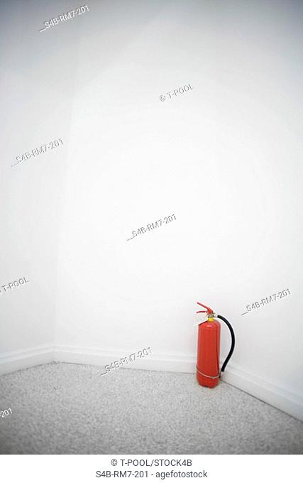 Fire extinguisher in front of a white wall