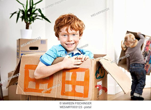 Happy boy looking out of a cardboard box in new apartment with sister in background
