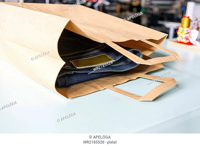 Close-up of jeans in paper bag at factory