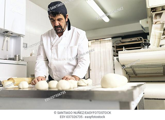 Baker kneading dough in a bakery. Bakery Concept
