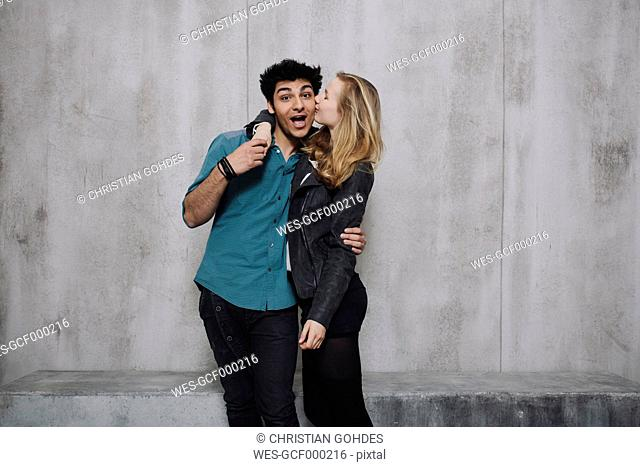 Couple in front of concrete wall, kissing