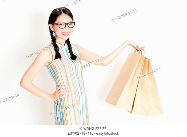 Portrait of young Asian female in traditional cheongsam dress shopping, hand holding paper bag, celebrating Chinese Lunar New Year or spring festival