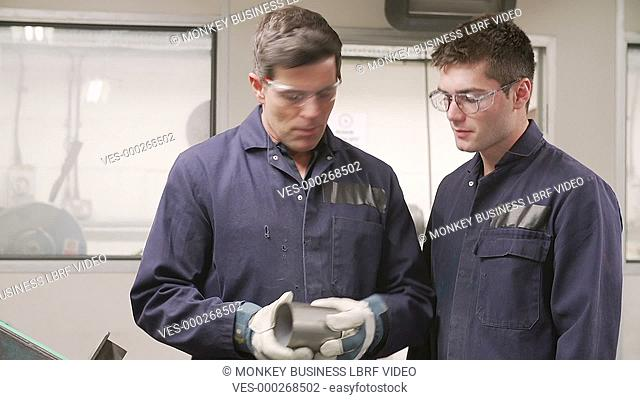 Engineer explaining to male apprentice how to operate grinding machine as he asks questions.Shot on Sony FS700 in PAL format at a frame rate of 25fps