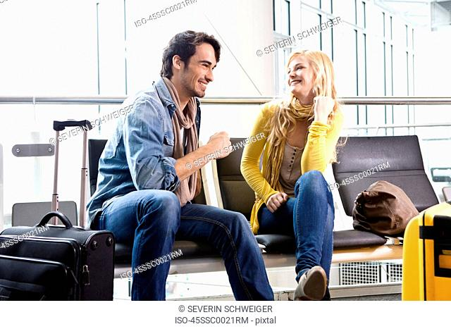 Couple talking in airport waiting area