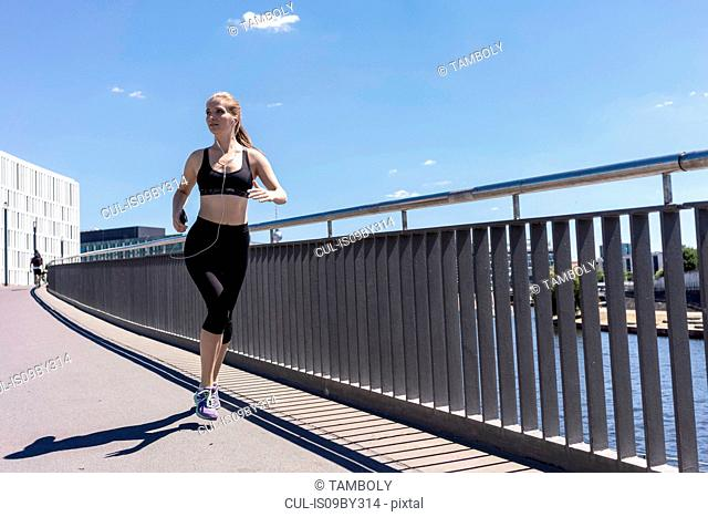 Young woman running in city, Berlin, Germany