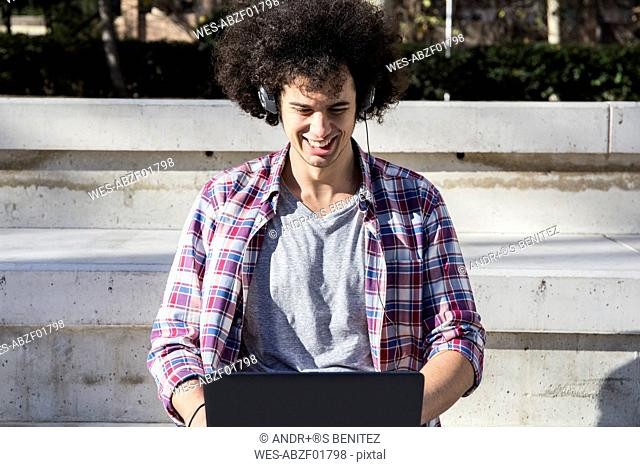 Smiling young man using laptop and headphones