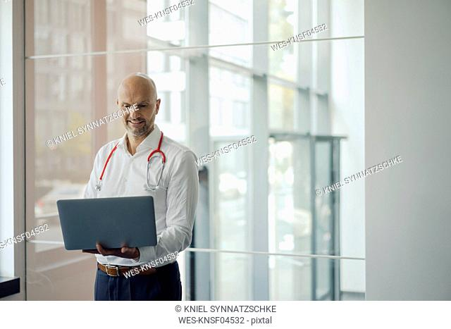 Doctor standing in hospital with stethoscope around his neck, holding laptop