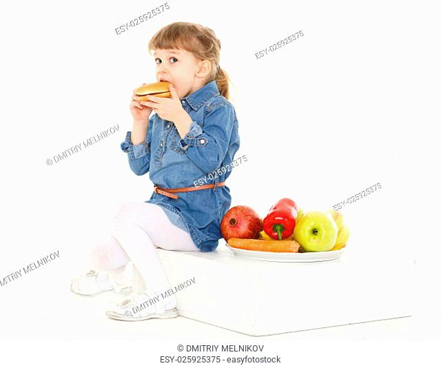 Little sweet girl with hamburger, fresh fruits and vegetables on a white background. Healthy and unhealthy food. 3 year old