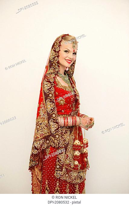 Portrait of a bride with blond hair wearing a red and gold sari, ludhiana punjab india