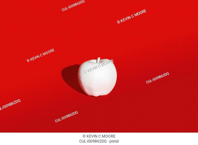Apple painted white on red background