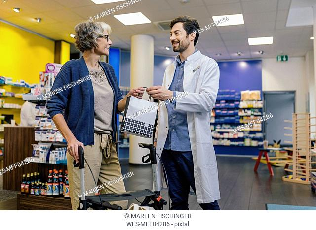 Pharmacist giving bag of medicine to customer with wheeled walker in pharmacy