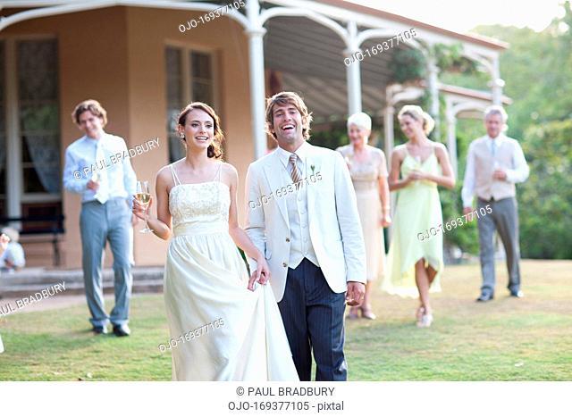 Bride, groom and guests walking across lawn