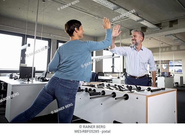 Two colleagues playing foosball and high fiving in office