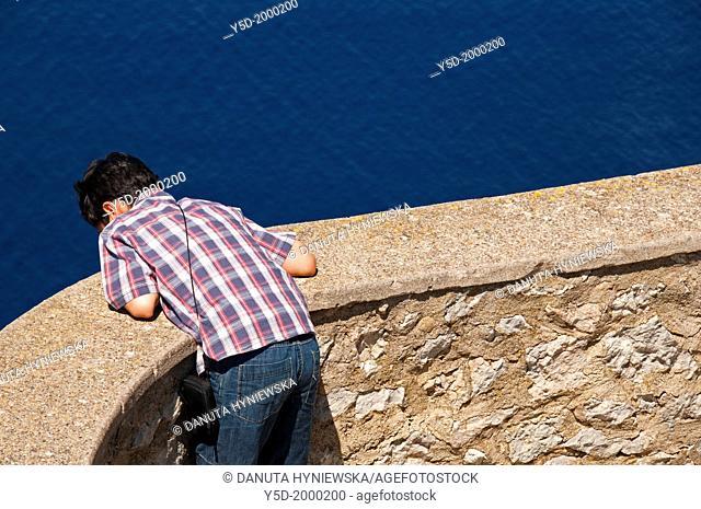 Boy looking down on Balearic Sea waters, Alcudia region, Majorca, Mallorca, Balearic Islands, Spain