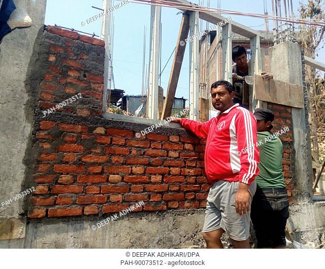 Teacher Dangal, who survived the earthquake in Nepal in 2015 in front of the re-building of his house in Irkhu, Nepal, 11 April 2017