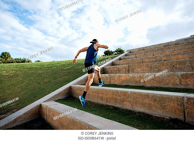 Young man exercising, running outdoors, leaping up steps, South Point Park, Miami Beach, Florida, USA